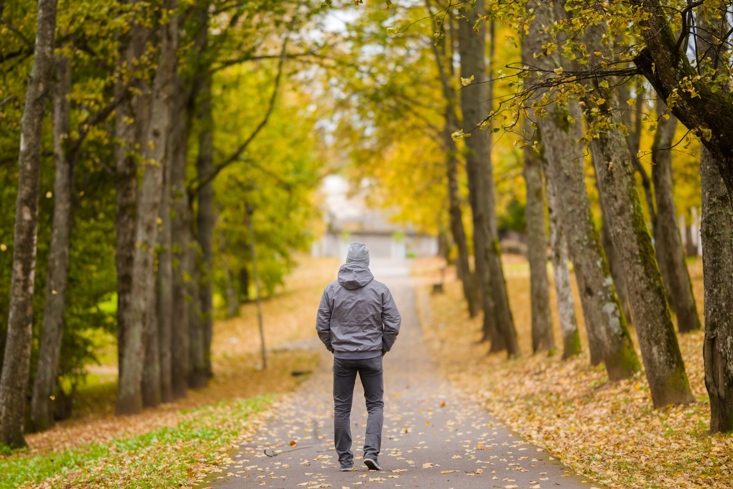 Man a wearing jacket walking through a park